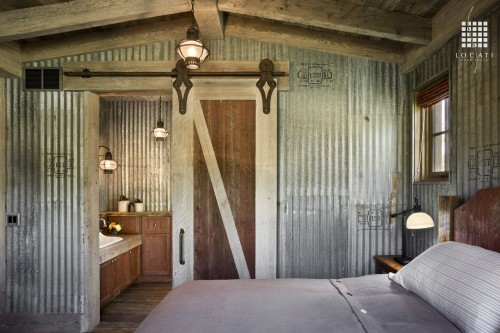 Locati Architects uses industrial metal on the walls of this bedroom to play up the rustic vibe.