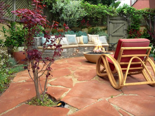 A Burgundy Leafed Tree And Red Cushions Complement This Flagstone Patio By  Urban Oasis.