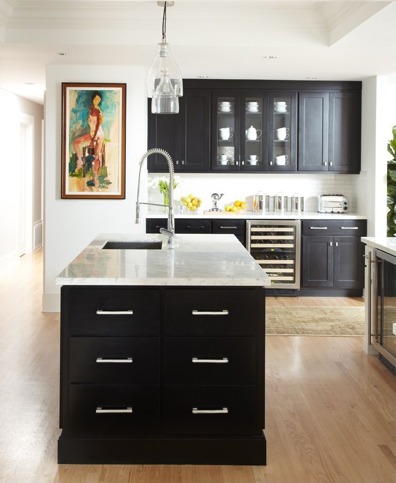 This Kitchen By Urrutia Design Showcases Black Cabinets With White Marble  Counters.