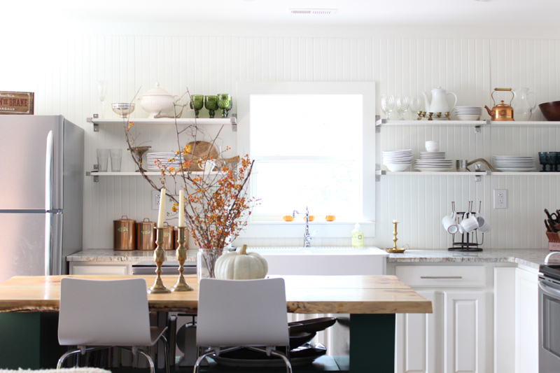Luxury White and stainless open shelves were used in place of upper cabinets for a modern take on the traditional open shelving found in farmhouse kitchens