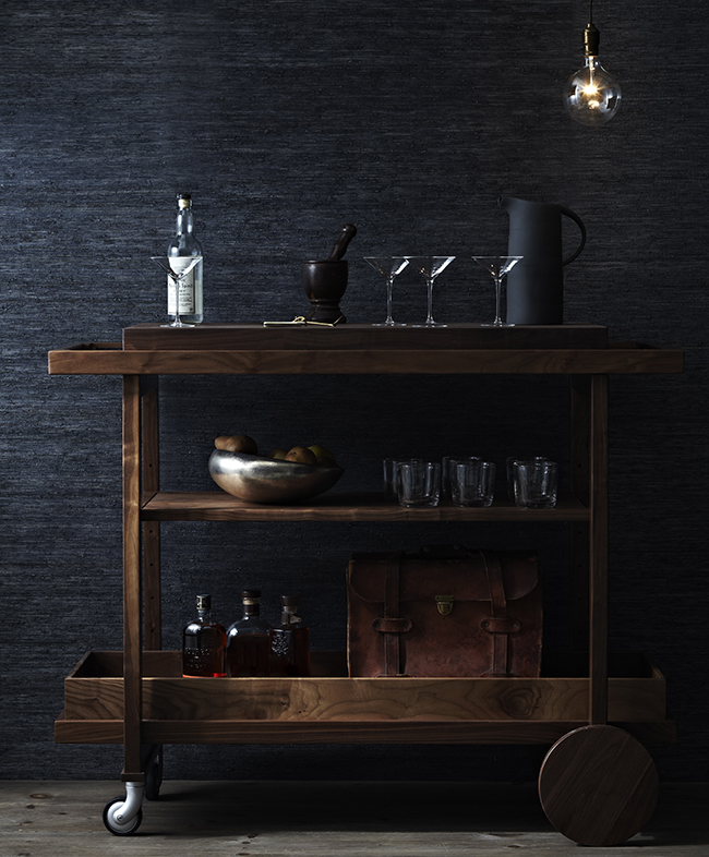 wooden bar cart against a black textured wall
