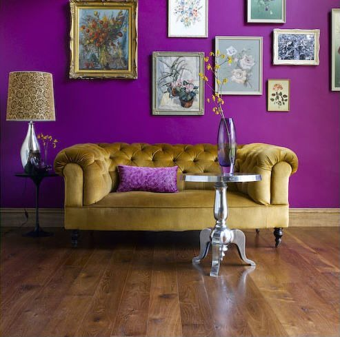A purple accent wall is a great backdrop for an art collection. Image by  Laura