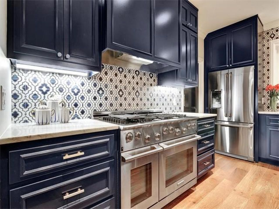 kitchen with navy blue cabinets and stainless steel appliances