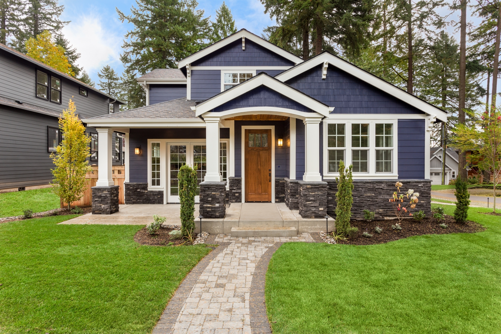 Blue traditional bungalow house with a slate gray paint and white edging.
