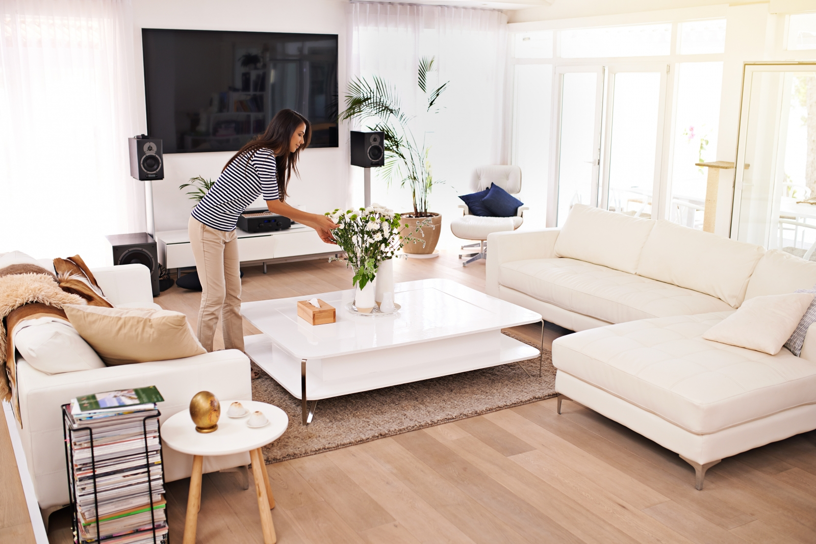 Woof floored living room decorated with modern white furniture, and a woman arranging flowers on the coffee table.
