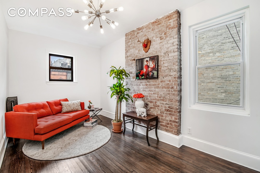 This Gut Renovated UWS Apartment Showcases Exposed Brick On The Fireplace  Wall.