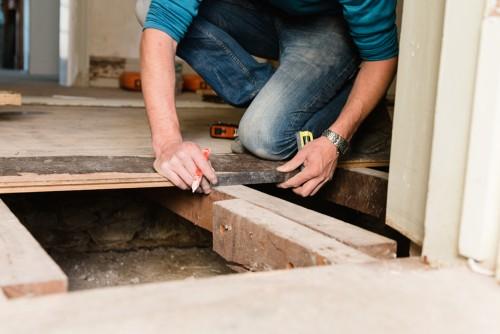man replacing old floor