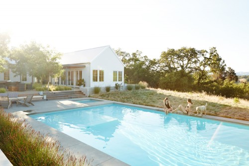 sisters sitting on edge of backyard pool home upgrade