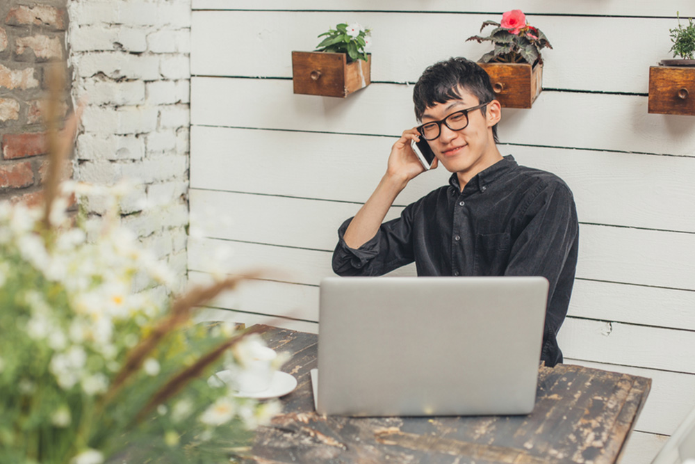 man on phone and laptop in garden