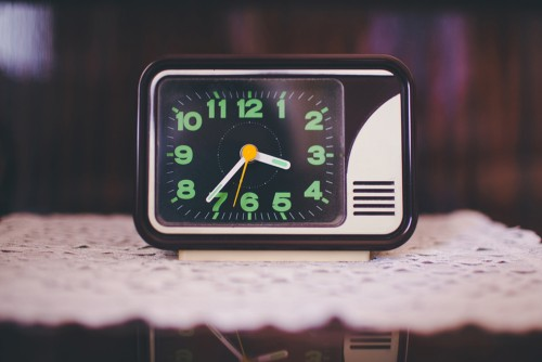alarm clock sitting on bedside table