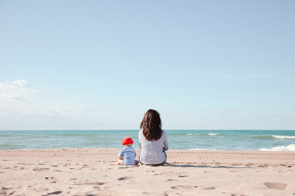 mother and child sitting at the beach