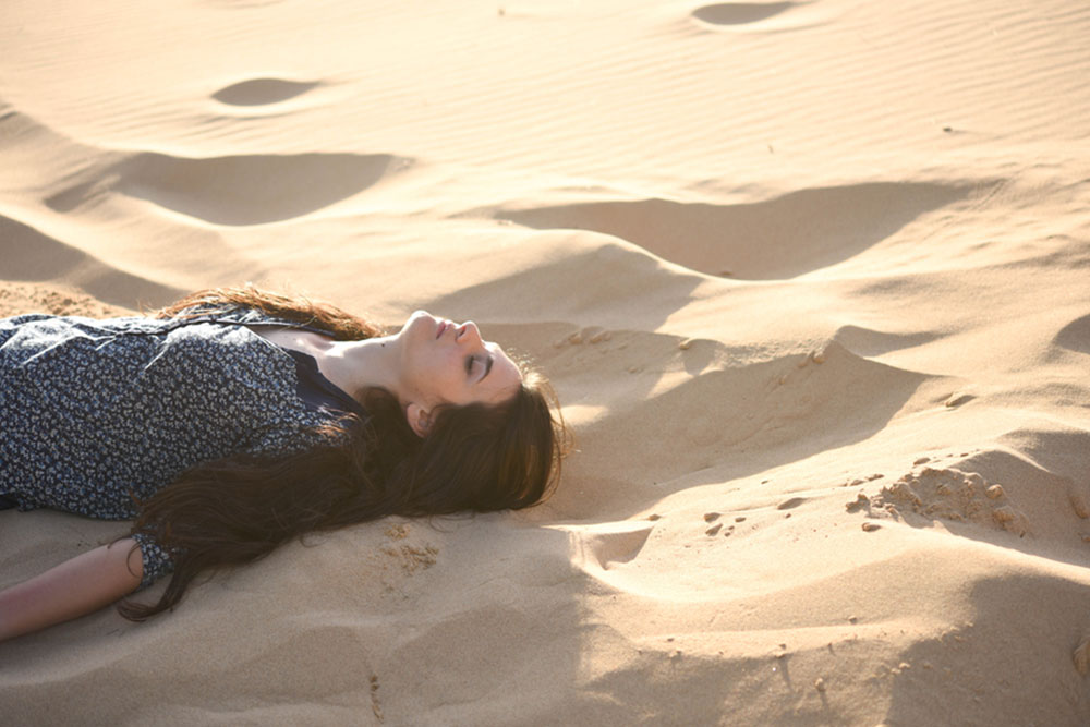 woman relaxing in sand