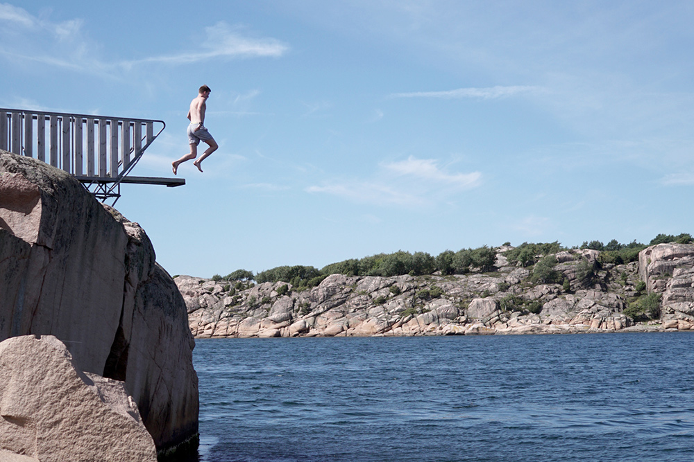 man jumping off high dive into lake