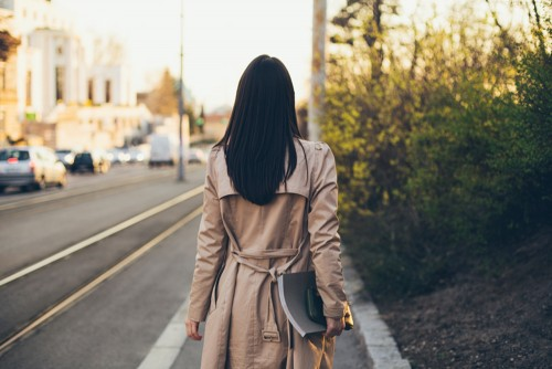 woman walking away with notebook and tablet
