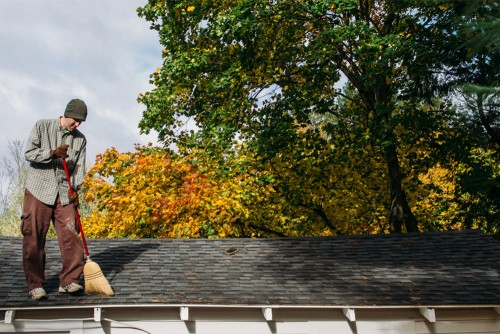 man sweeping roof