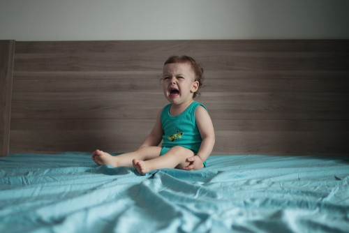 toddler crying on bed