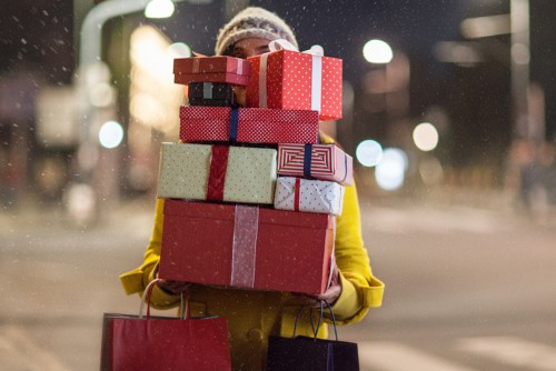 woman carrying stack of gifts