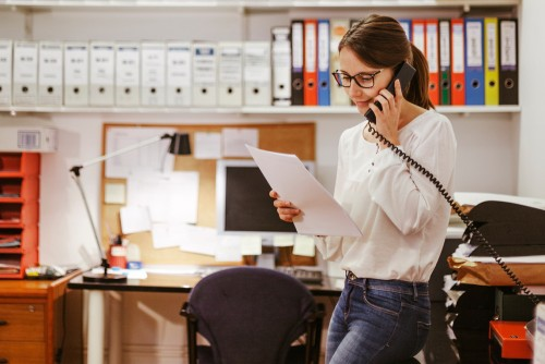 woman talking on phone looking at real estate attorney paperwork