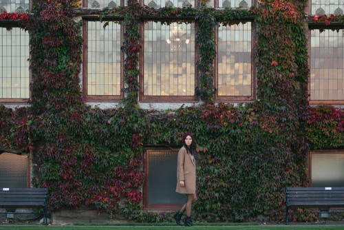 woman walking by ivy building