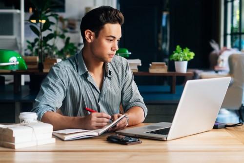 young man at computer doing mortgage calculation