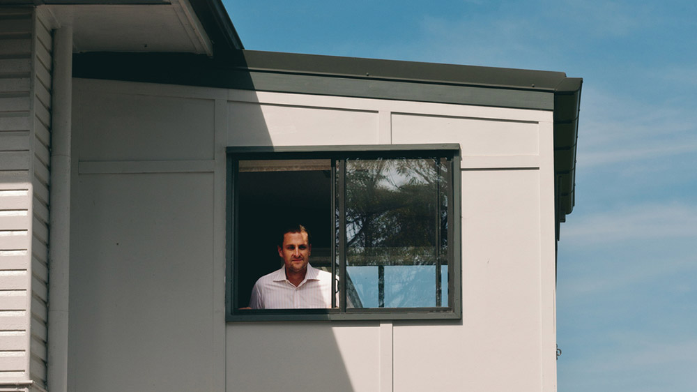 man looking out window during house appraisal