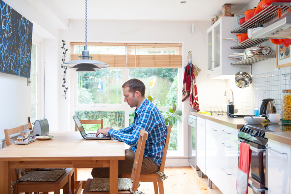 Man On Computer Researching Kitchen Remodeling Plans