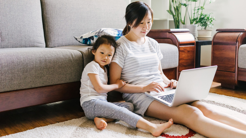 woman and daughter compare home insurance on laptop in home
