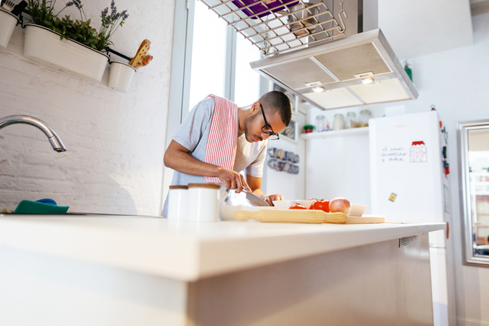 man being careful cooking so he can get his security deposit refund