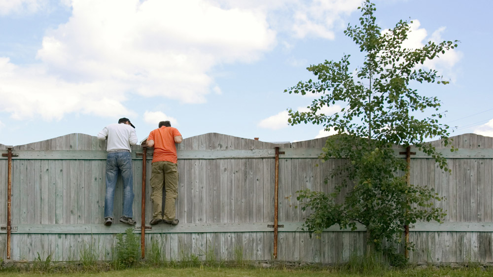 men looking over fence finding out property rights