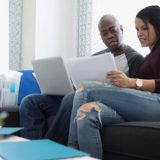 Couple with laptop budgeting in living room
