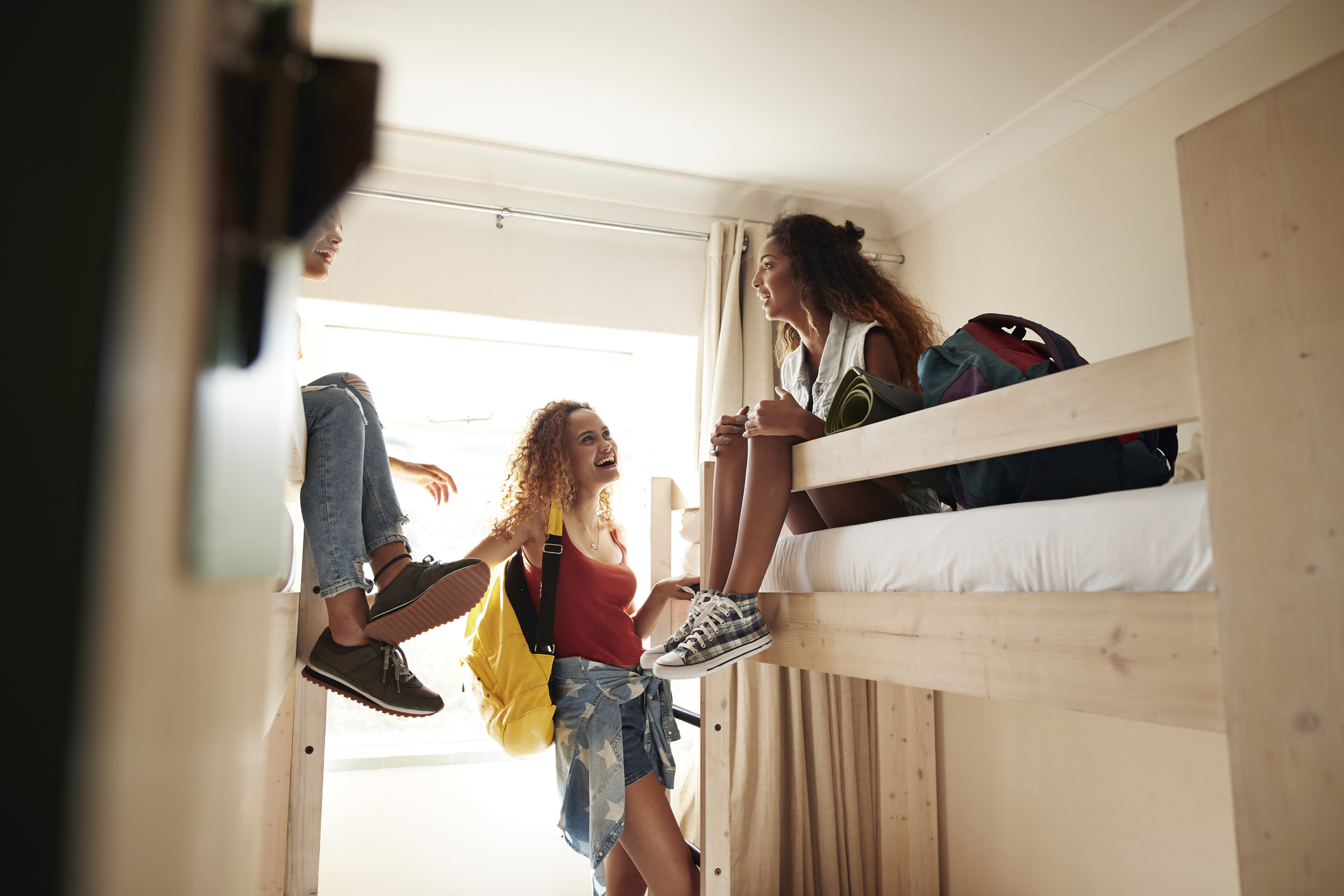 Young women arriving to room with bunk beds, at college dorm